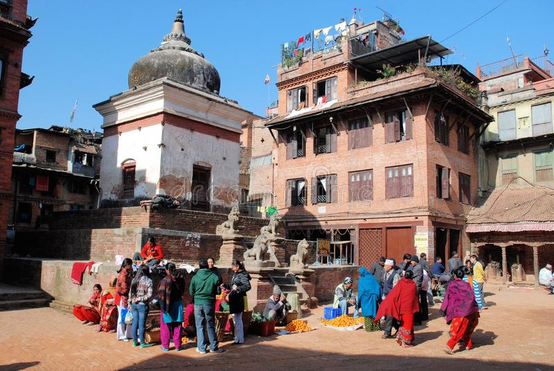 Street life Bhaktapur Nepal with Temple and local. Street life Bhaktapur Nepal with small temple, sellers and colored dressed local people royalty free stock images