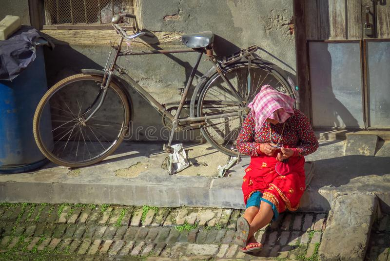 Street life in Nepal, woman sitting on the curb clipping her nails, Bhaktapur. Bhaktapur, Nepal - 11/21/2017: Everyday life, woman sitting on the curb clipping royalty free stock images