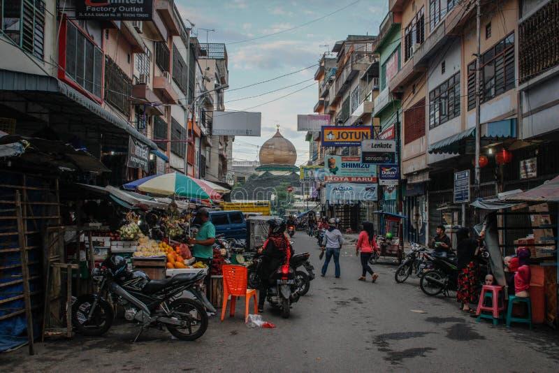 Street life - shops, fruit vendors, motorbikes and pedestrians royalty free stock photos