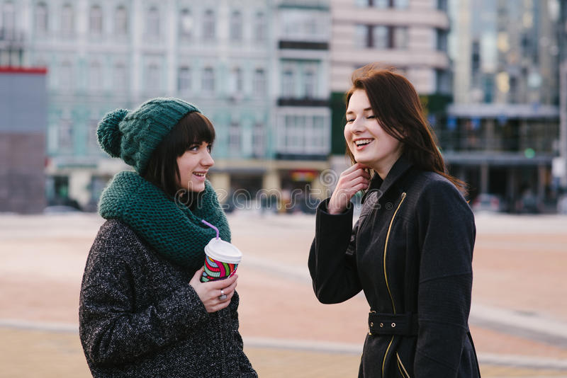 Street Lifestyle portrait of two beautiful, smiling and very stylish girls who communicate with each other royalty free stock photos