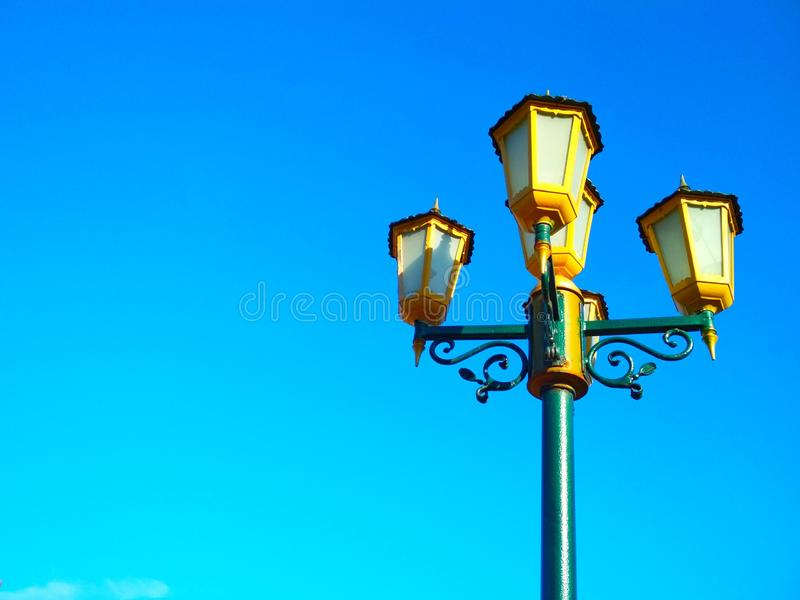Street light, architectural decision. View of a street light against the background of the blue cloudless sky stock image