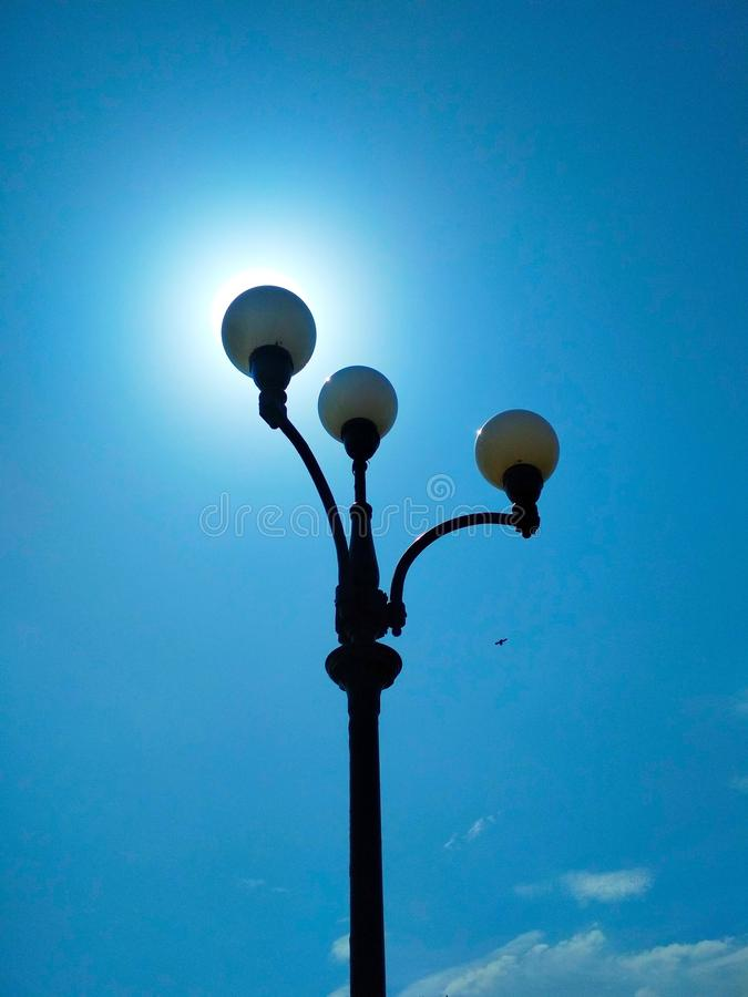 Street light, architectural decision. View of a street light against the background of the blue cloudless sky and shining sun stock image