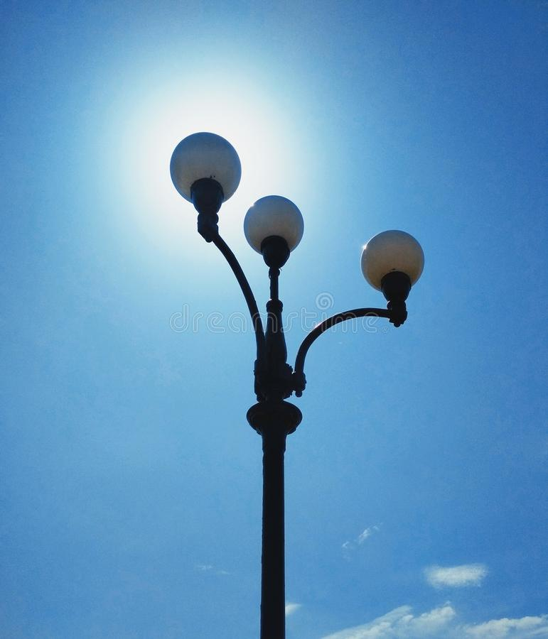 Street light, architectural decision. View of a street light against the background of the blue cloudless sky and shining sun stock photography