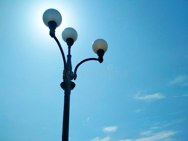Street light, architectural decision. View of a street light against the background of the blue cloudless sky and shining sun royalty free stock photos
