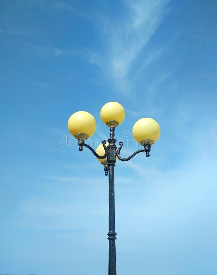 Street light, architectural decision. View of a street light against the background of the blue cloudy sky royalty free stock photo