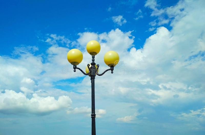 Street light, architectural decision. View of a street light against the background of the blue cloudy sky royalty free stock image
