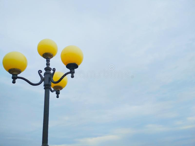 Street light, architectural decision. View of a street light against the background of the blue cloudy sky royalty free stock images
