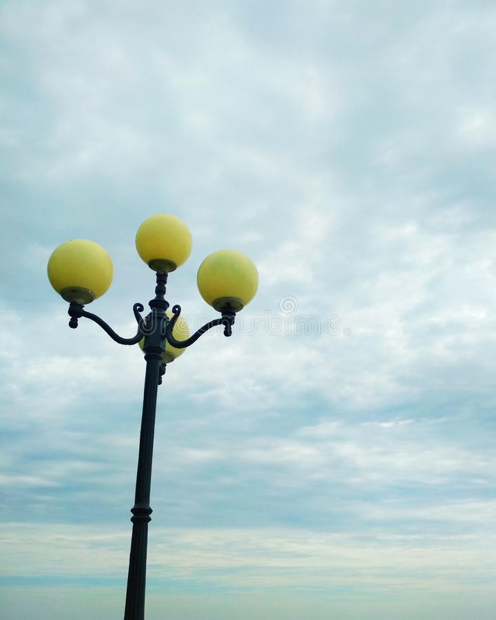 Street light, architectural decision. View of a street light against the background of the sky covered with clouds royalty free stock image