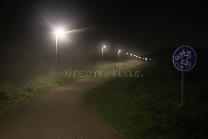 Street lights in the fog at the small bicycle lane between Capelle en Nieuwerkerk aan den IJssel. stock photo