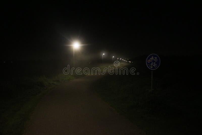 Street lights in the fog at the small bicycle lane between Capelle en Nieuwerkerk aan den IJssel. royalty free stock image