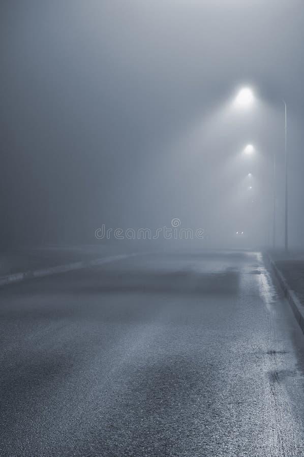 Street lights, foggy misty night, lamp post lanterns, deserted road in mist fog, wet asphalt tarmac, car headlights approaching stock images
