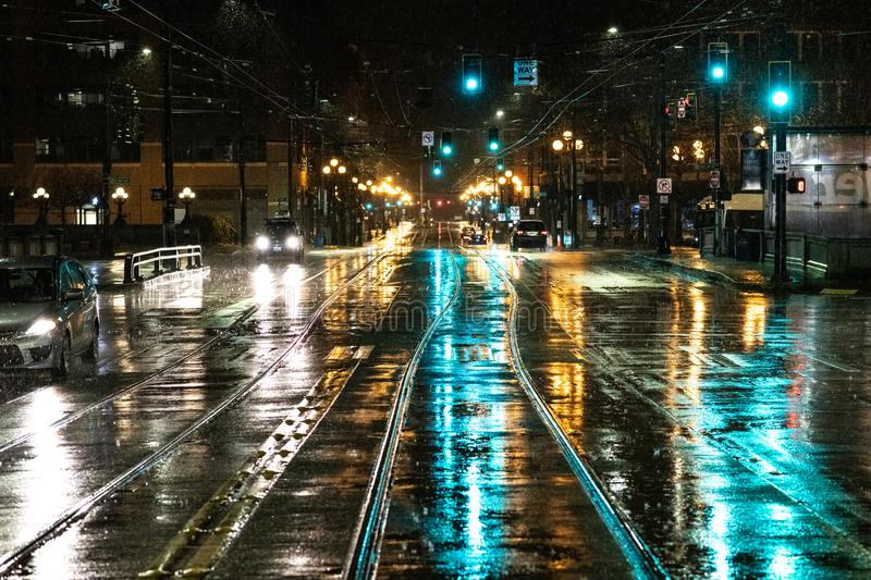 Street lights reflecting off of a wet downtown street stock photos