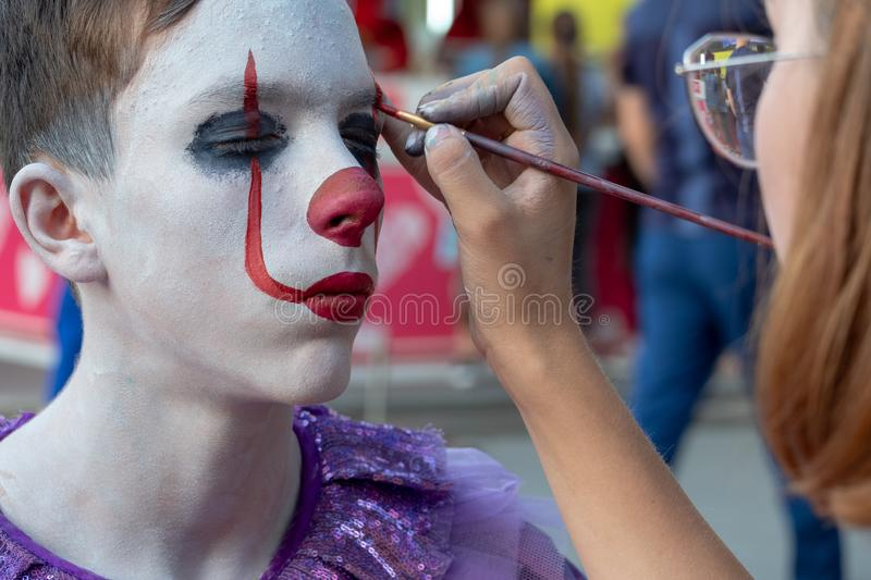 Street makeup for halloween. The make-up artist paints the guy`s face like a clown Pennywise. A teenager in an IT costume on a stock photography