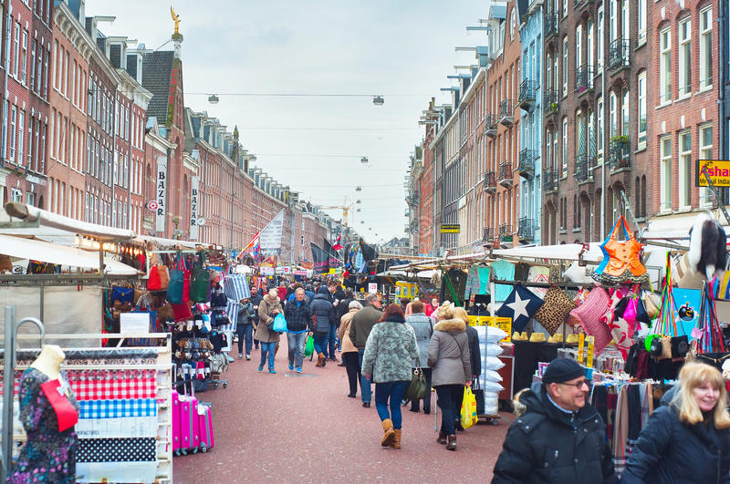 Street market Amsterdam. AMSTERDAM, NETHERLANDS - FEB 14, 2014: People at Albert Cuyp Market in Amsterdam. The market began trading in 1904, now over 300 stalls stock photo