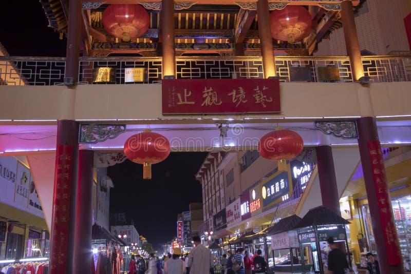 Street market, Dunhuang, China at night. Dunhuang, Gansu, China - September 12, 2018 : Street market of Dunhuang, China illuminated at night crowded with stock photos