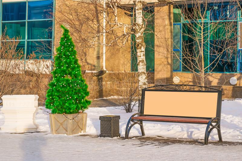 Street mock up, blank Billboard next to the Christmas trees decorate the streets of the city for the New year, royalty free stock image
