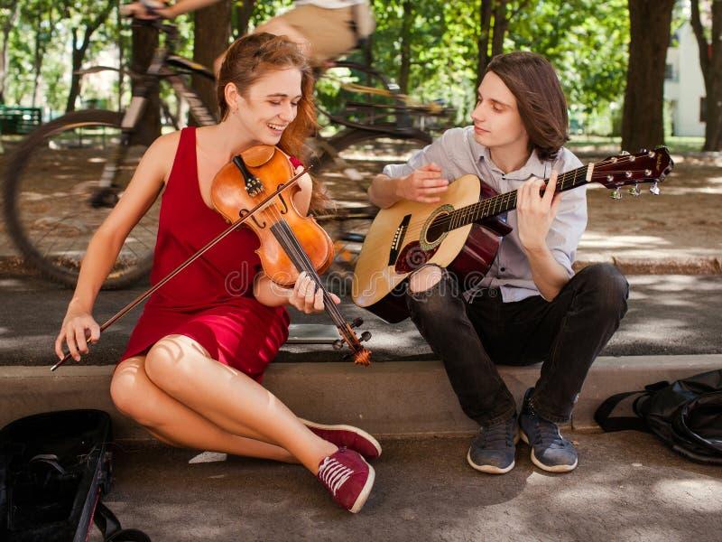 Street music duo performance romance freedom. Street music duo group performing in a park. free spirits hippie romance concept stock image