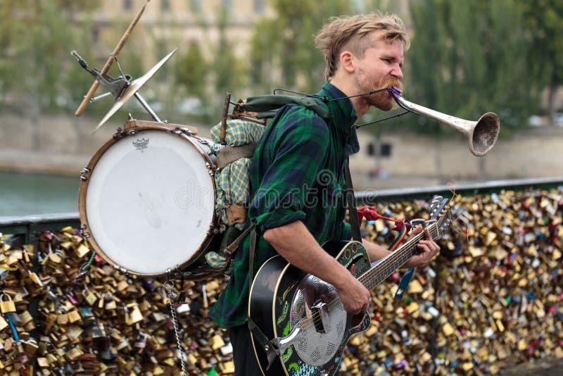 Street musician busker entertain public on Pont des Arts in Paris. PARIS, FRANCE - SEPTEMBER 11, 2014: A street musician busker entertain public on Pont des Arts stock photo