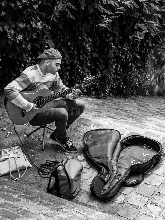Street musician is playing guitar outdoor in the Montmartre dist stock photography