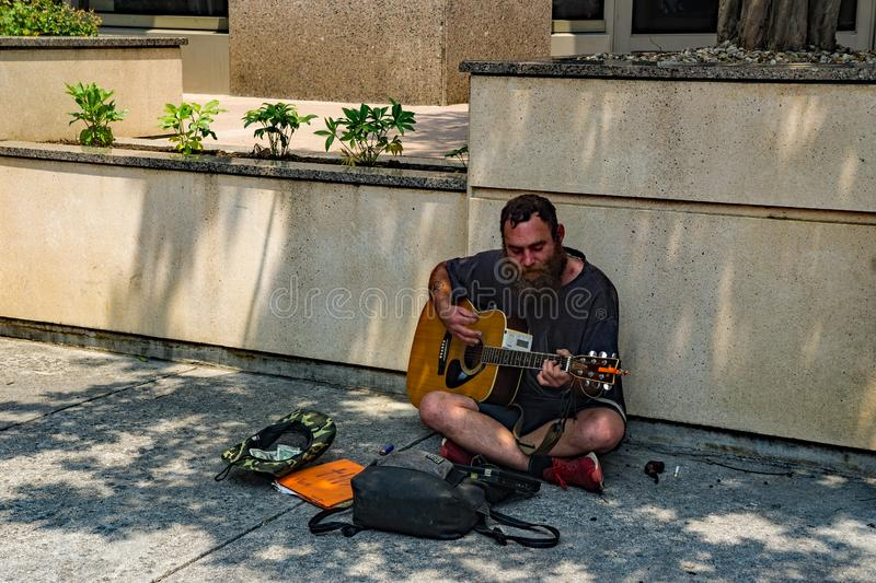 Street Musician Playing a Guitar for Tips royalty free stock photography