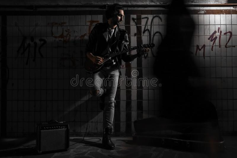 A street musician playing on guitar in the underpass. Vagrant lifestyle. Playing in the underpass to make a living. Unemployed. Musician. Future rock star royalty free stock photography