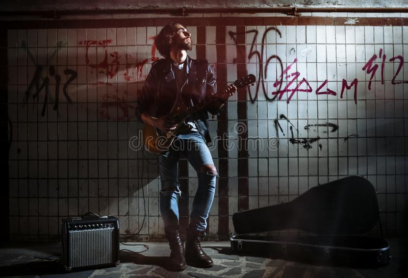 A street musician playing on guitar in the underpass. Vagrant lifestyle. Playing in the underpass to make a living. Unemployed. Musician. Future rock star royalty free stock photos