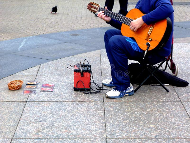 Street musician in public square playing guitar. city pigeon nearby royalty free stock images