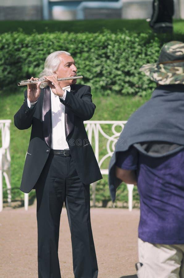 Street musician senior man plays the flute stock photos