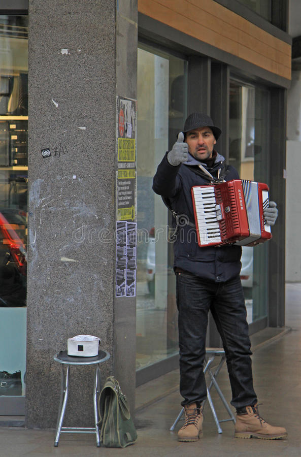 Street musician is showing a thumb to someone stock photo
