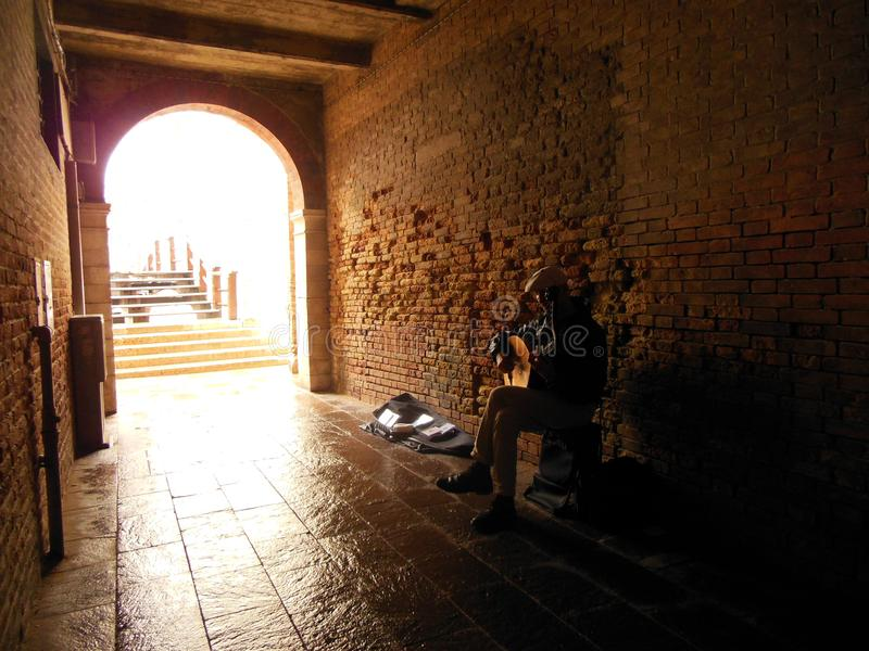 Street Musician, Venice, Italy. A street musician playing a lute in a covered passageway that connects to one of Venice's many bridges royalty free stock image