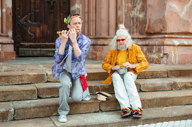 Street musicians playing music sitting on stairs stock images