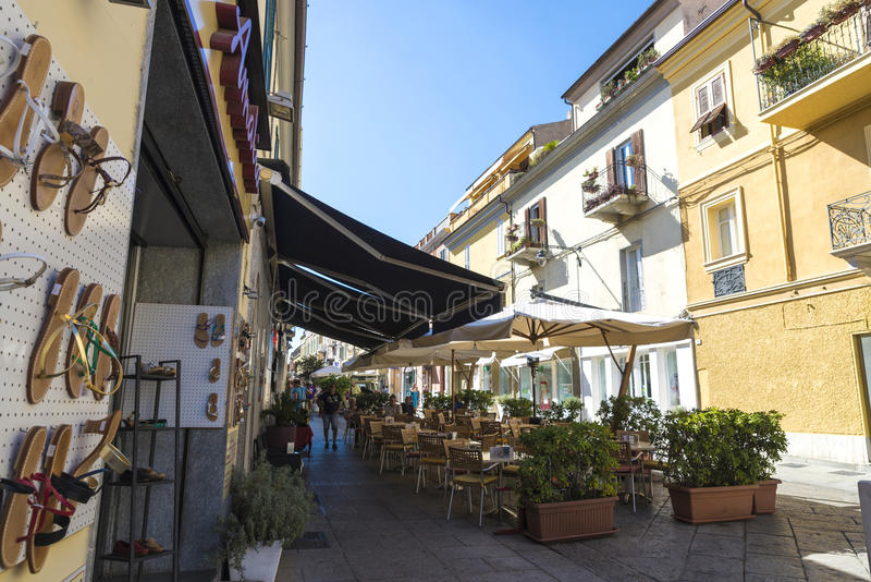 Street in Olbia, Sardinia, Italy. Olbia, Italy - August 24, 2016: Street of the old town of Olbia with people walking and bar terraces in Sardinia, Italy in royalty free stock image