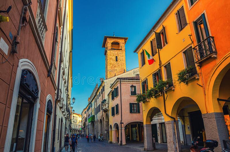 Street with old colorful buildings with italian flag on wall and tower in medieval historical city centre of Padua. Evening twilight view, Padova town, Veneto royalty free stock image