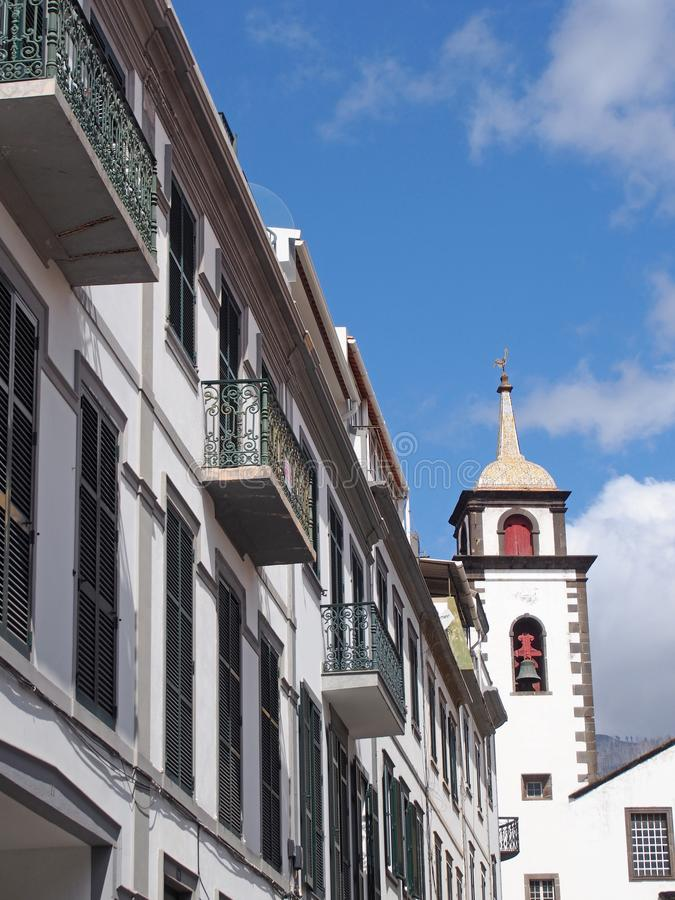 Street of old white painted houses and the tower of the historic parish church of saint peters in funchal madeira famous for being stock images
