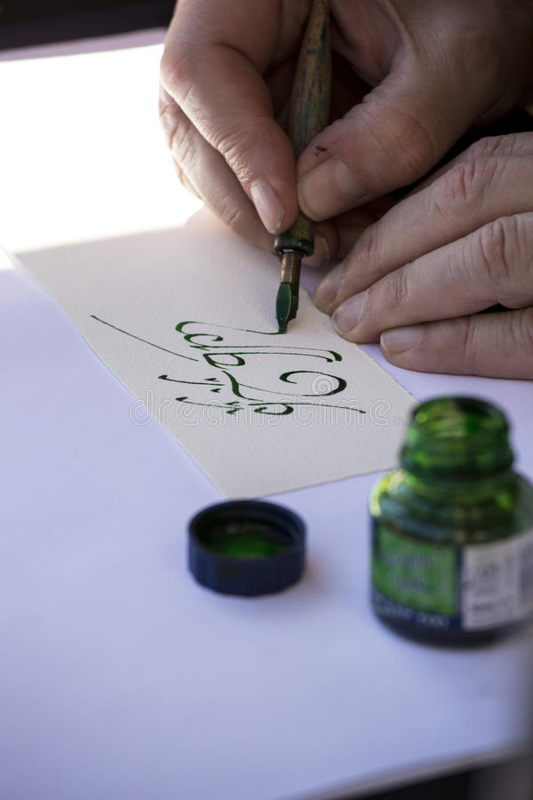 Street painter writing a celtic name with green pen.  royalty free stock photo