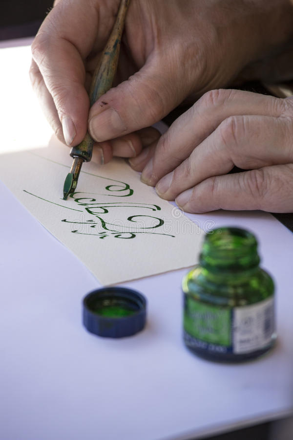 Street painter writing a celtic name with green pen.  royalty free stock photography