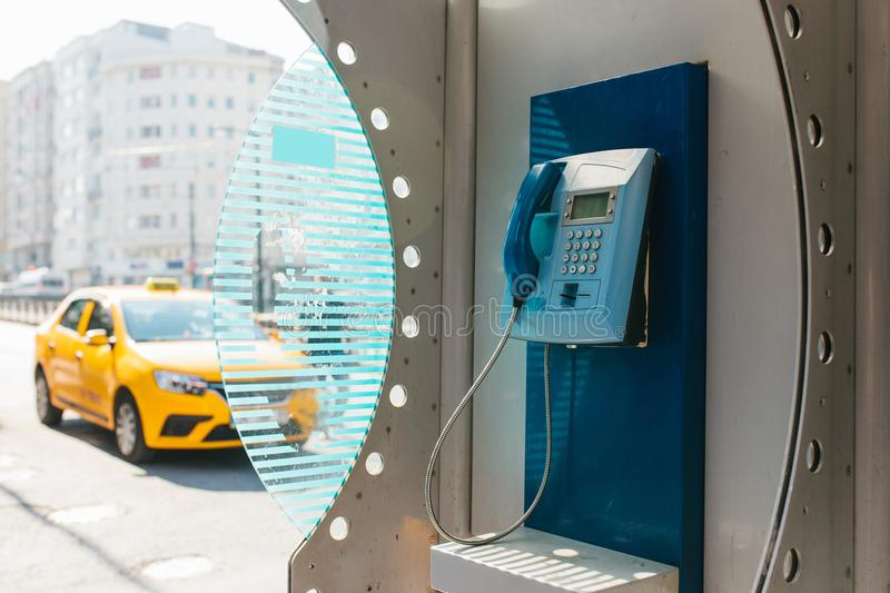 Street payphone with yellow taxi in the background. Travel concept, passenger transportation, communication. City. Street payphone with yellow taxi in the stock photo