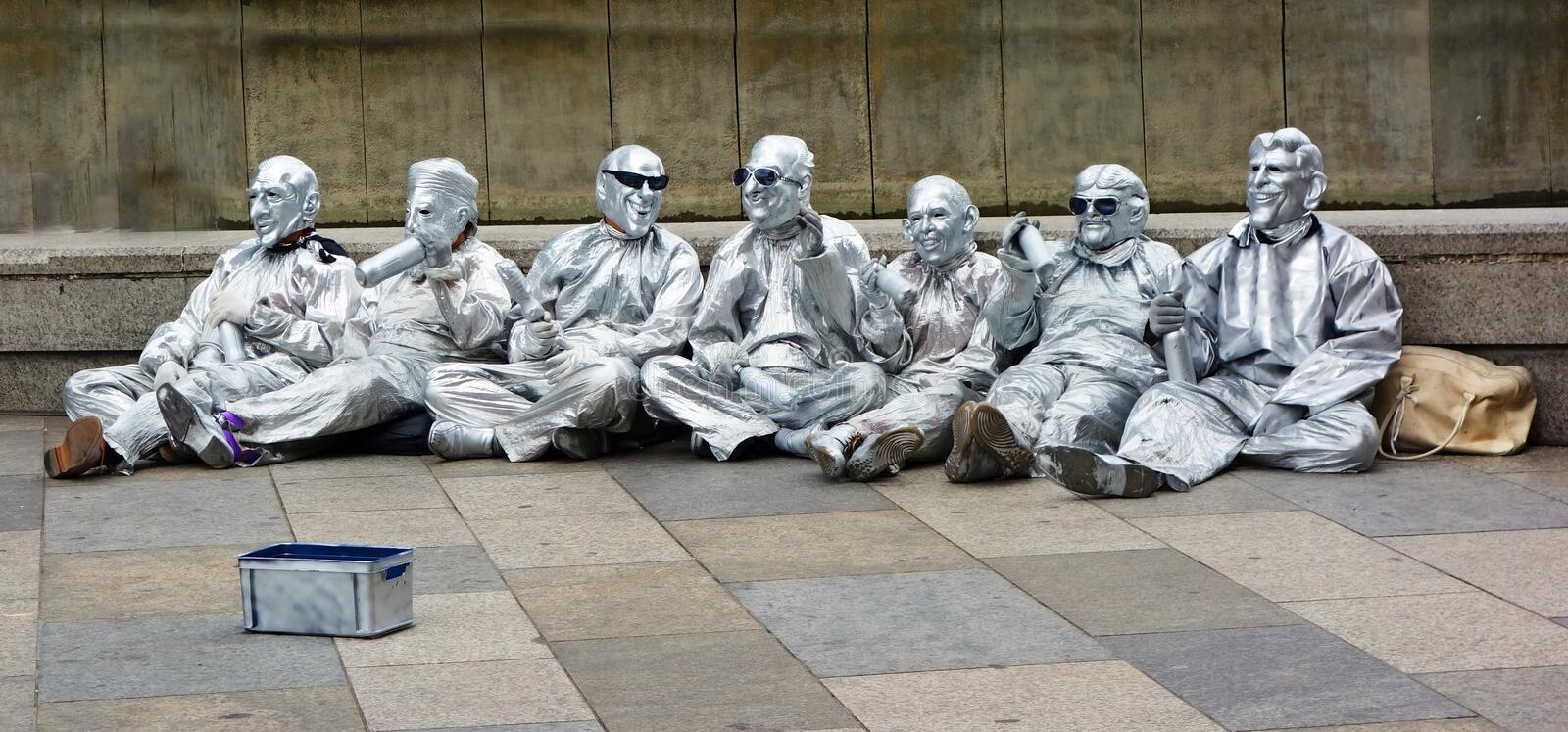 Street perfomance. A group of silvery costumed artists siiting motionless on the ground , begging for money. Ohoto was taken in august 2013 royalty free stock photo