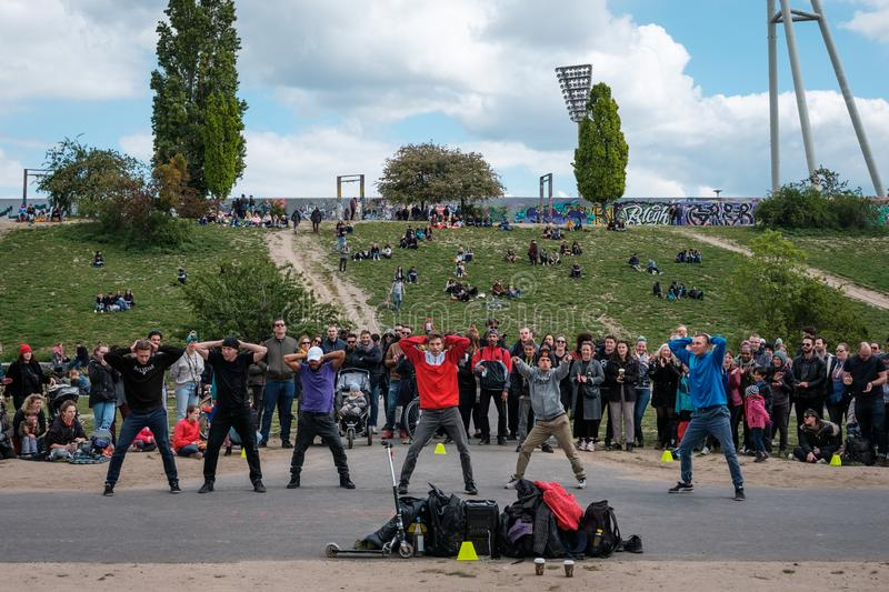 Street performer group dancing breakdance in crowded park Mauerpark in Berlin. Berlin, Germany - May, 2019: Street performer group dancing breakdance in crowded stock photography