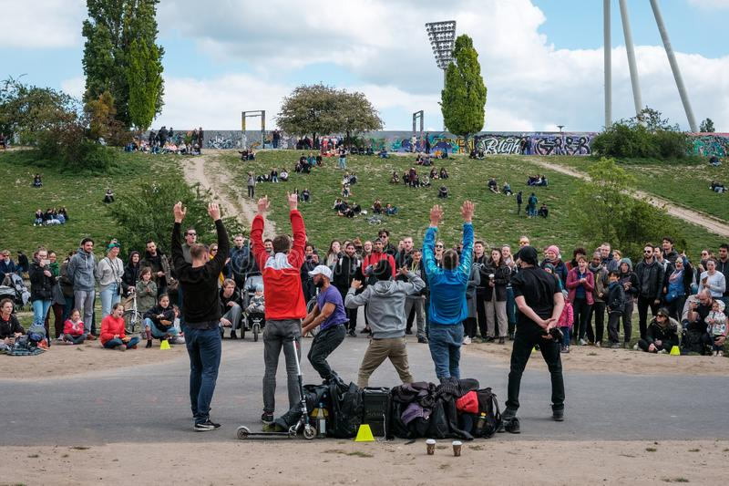 Street performer group dancing breakdance in crowded park Mauerpark in Berlin. Berlin, Germany - May, 2019: Street performer group dancing breakdance in crowded royalty free stock images