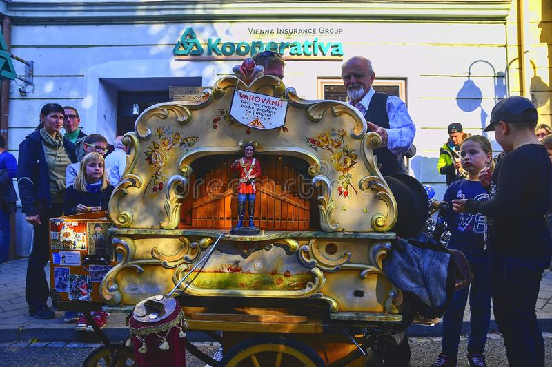 Street performer playing on a barrel organ. Barrel organs are valuable because they preserve old styles of musical ornamentation. HUSTOPECE, CZECH REPUBLIC stock photo