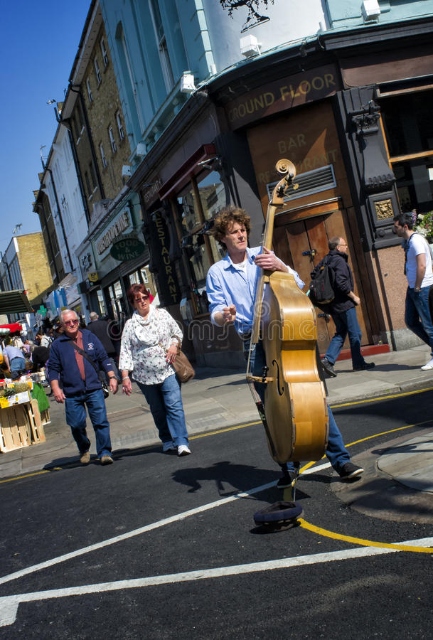 Street Performer, Portobello, London, England. A street performer, or busker, plays his bass violin on a beautiful day at the Portobello Road Market, in the stock photos