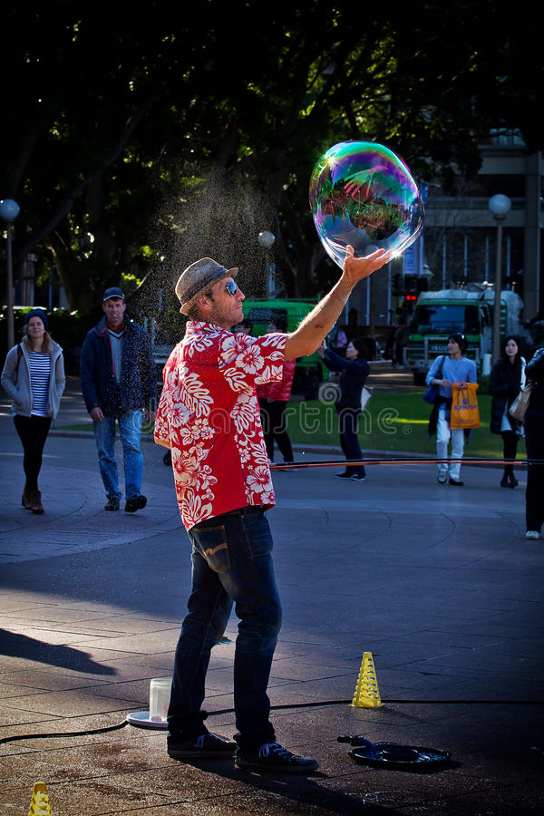 Street performer spins a soap bubble royalty free stock photography