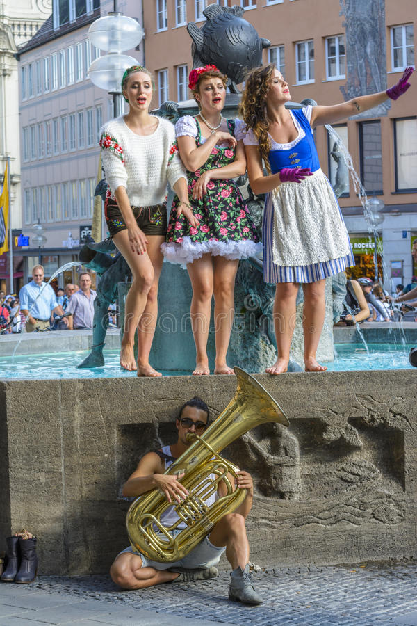 Street performers, dressed in Bavarian traditional costumes. Sing in Marienplatz on June 29, 2015 in Munich, Bavaria, Germany. Marienplatz is a central square royalty free stock images