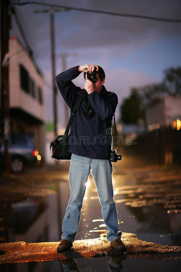 Street photographer. Photographer shooting at twilight in a city stock photography