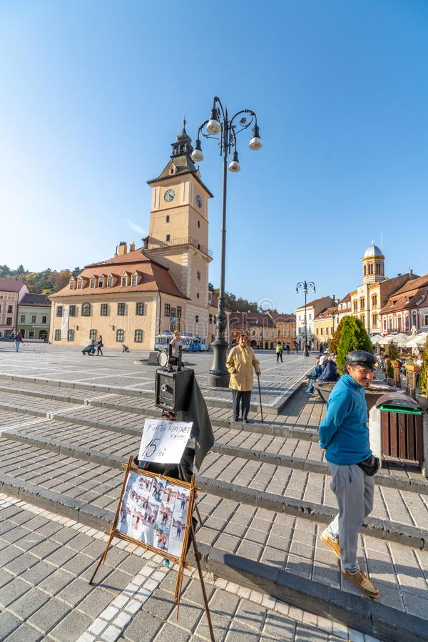 Street photographer on the central square of the old Brasov in Romania. One of the ten largest cities in Romania. Located in the heart of Romania, the city of stock image