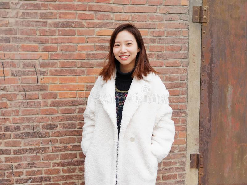 Street photography of a beautiful Chinese woman in white coat with red brick wall background, smiling with two hand in her pocket stock photo
