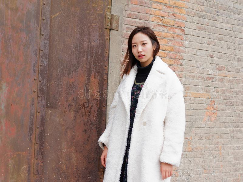 Street photography of a beautiful Chinese woman in white coat with red brick wall and rusty iron door background, looking at you stock photos