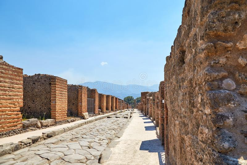 A street in Pompeii. A street without people with the ruins of houses in Pompeii with Vesuvius in the background stock photo