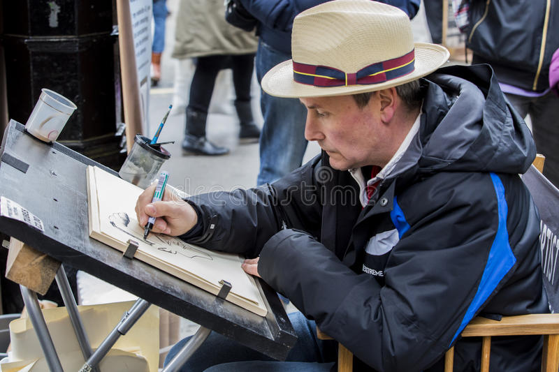 Street portrait artist. YORK, UK - 26 MARCH 2016. Street portrait artist drawing caracture of customer royalty free stock images